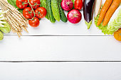 Assorted raw organic fresh vegetables on white wooden table. Fresh garden vegetarian food. Autumn seasonal image of farmer table with mushrooms, rye, cucumbers, tomatoes, eggplant, cabbage, carrots