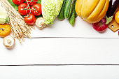 Assorted raw organic fresh vegetables on white wooden table. Fresh garden vegetarian food. Autumn seasonal image of farmer table with mushrooms, rye, cucumbers, tomatoes, eggplant, pumpkin and other