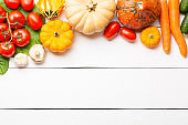Assorted raw organic fresh vegetables on white wooden table. Fresh garden vegetarian food. Autumn seasonal image of farmer table with mushrooms, rye, cucumbers, tomatoes, eggplant, pumpkins