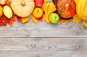 Pumpkins with colorful maple leaves, ripe apples, ashberry and pear on wooden background. Autumn thanksgiving seasonal image with free space for your text