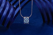 Elegant pave pendant necklace with blue and white gemstones on blue background