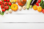 Assorted raw organic fresh vegetables on white wooden table. Fresh garden vegetarian food. Autumn seasonal image of farmer table with mushrooms, pumpkin, cucumbers, tomatoes, eggplant and onion.