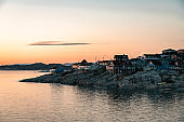Aerial View of Arctic city of Ilulissat, Greenland during sunrise sunset. Colorful houses in the center of the town with icebergs in the background in summer on a sunny day with orange pink sky
