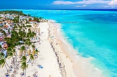Aerial drone view of beautiful atlantic tropical beach with palms, straw umbrellas and boats. Bavaro, Punta Cana, Dominican Republic. Vacation background.