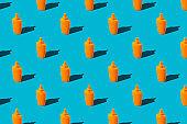 Summer vacation minimal concept. Pattern of orange sunscreen lotion bottles on blue background