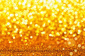 Gold yellow glitter foil background. Shiny metal gold foil texture abstract defocused background. Sparkle glitter texture with bokeh lights