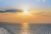Sunset Sailing. Seascape image with shiny sea and sailboat over cloudy sky and sun during sunset on Apulia coast, Italy.