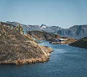 Colorful houses dot the hillsides of the fishing town of Kangaamiut, West Greenland. Icebergs from Kangia glacier in Greenland swimming with blue sky and clouds. Symbol of global warming.