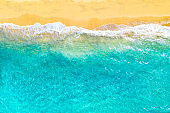 Summer vacation background. Drone aerial view of turquoise ocean waves and the sandy coastline. Exotic tropical beach in Dominican Republic