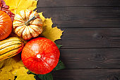 Autumn backdrop decoration with pumpkins and colorful leaves on dark wooden table. Free space