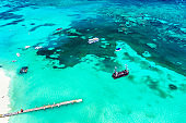 Aerial drone view of beautiful atlantic ocean with pirate ship and boats. Bavaro, Punta Cana, Dominican Republic. Vacation background.