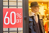 Male mannequin near sign with discount inscription SALE 60 in a clothing store
