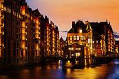The Warehouse district Speicherstadt during twilight sunset in Hamburg, Germany. Illuminated warehouses in Hafencity quarter in Hamburg.