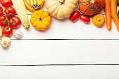 Organic fresh vegetables food background. Autumn vegetables and Thanksgiving day theme. Pumpkins, carrots, tomatoes, mushrooms, cucumbers, corn and garlic on white wooden table. Free space