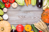 Assorted raw organic fresh vegetables on wooden table. Fresh garden vegetarian food. Autumn seasonal image of farmer table with mushrooms, rye, cucumbers, tomatoes and eggplant. Free space.