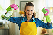 smiling woman with cleaning agent and sponge showing biceps
