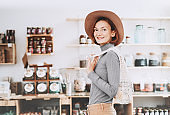 Minimalist vegan style young woman with cotton reusable net mesh bag on background of goods of zero waste shop.