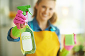 happy woman with sponge showing cleaning agent