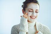 smiling stylish woman applying white facial mask