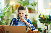 pensive trendy woman with laptop in modern house in sunny day