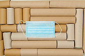 flat lay with medical mask on toilet paper tubes background