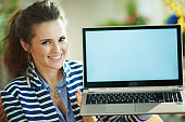 happy modern woman and showing laptop blank screen