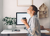 Modern smiling beautiful woman working and drinking coffee from reusable mug at home office.