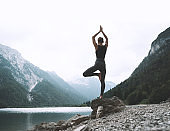 Young woman is practicing yoga at mountain lake. Girl doing yoga on nature.