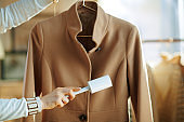 Closeup on housewife cleaning coat on hanger with lint roller