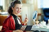 smiling modern woman using concealer palette