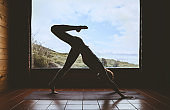 Silhouette of young woman practicing yoga indoor on background of big window with natural landscape.