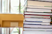 Stack of books on table in school library on blurry background. Concept back to school. Close-up, copy space