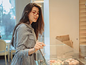 A beautiful young asian girl with long hair chooses a dessert in a cafe by the window. Beautiful interior of bakery cafe