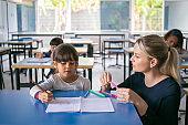 Serious primary school teacher helping girl