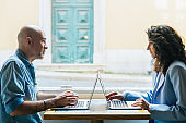 Focused people talking while sitting at table with laptops