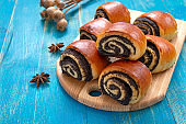 Tasty buns rolls with poppy filling on a blue wooden background.