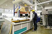 Back of male technician operating milling machine