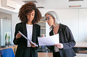 Content young manager showing document to adult colleague