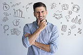 Successful man rubbing chin with hand drawn business sketches