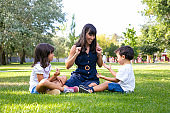 Cheerful mom and two kids sitting on grass