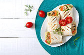 Fresh tortilla wraps with chicken, mushrooms and fresh vegetables. Chicken Mexican burrito. Tasty appetizer. Dishes from pita bread. Healthy food concept