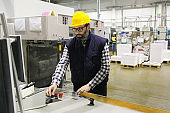 Focused male factory worker operating machine