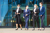 Group of female colleagues in office suits and masks