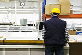 Rear view of male factory worker operating milling machine