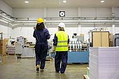 Back view of female factory workers walking and talking