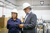 Male engineer and female factory worker in hardhats
