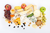 Plenty of various cheeses, fruits, nuts and toasted bread