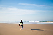 Back view of surfer standing on sand beach with board