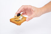 Human hand holding toasted slice of bread with blue cheese