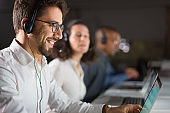 Smiling bearded call center operator working